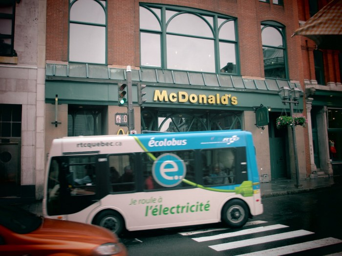 A cute eco-bus passing the MacDonald's in unique green exterior ;)